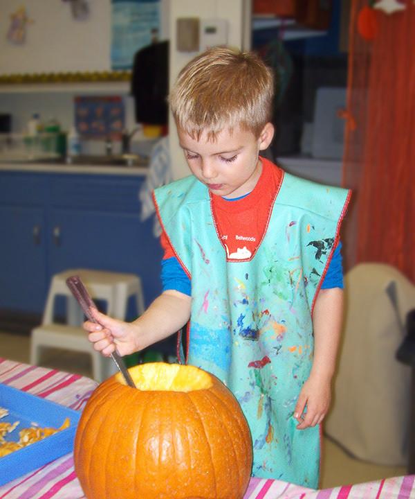 Whitehaven boy carving pumpkin